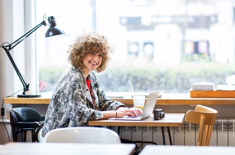 Jeune femme travaillant sur son ordinateur portable en café image libre de droits