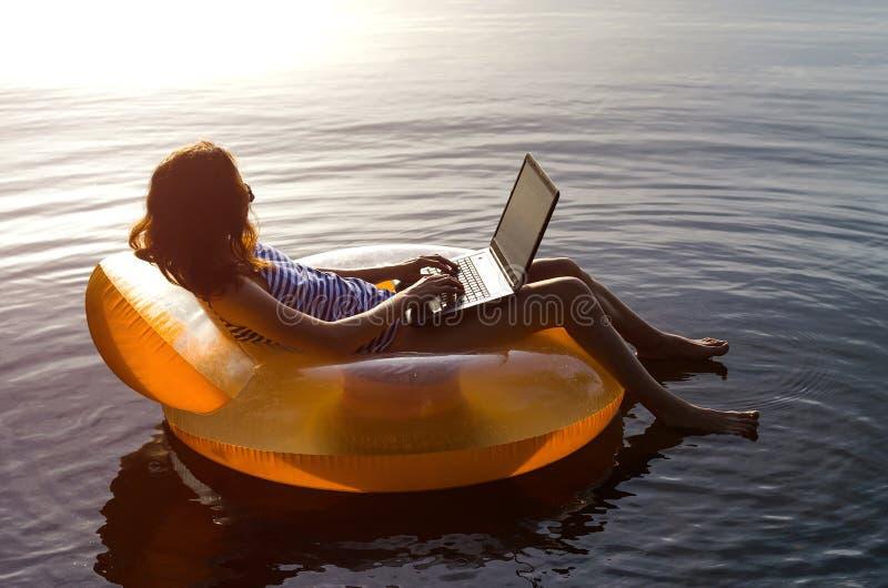 Jeune femme travaillant sur un ordinateur portable dans l'eau sur un ri gonflable photographie stock libre de droits