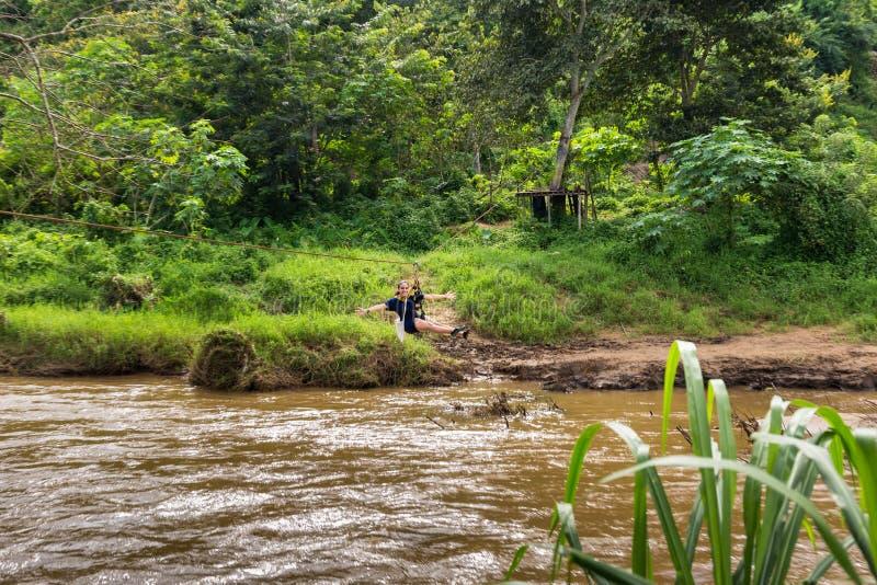 Jeune femme traversant la rivière sur la ligne de fermeture éclair en Chiang Mai images stock