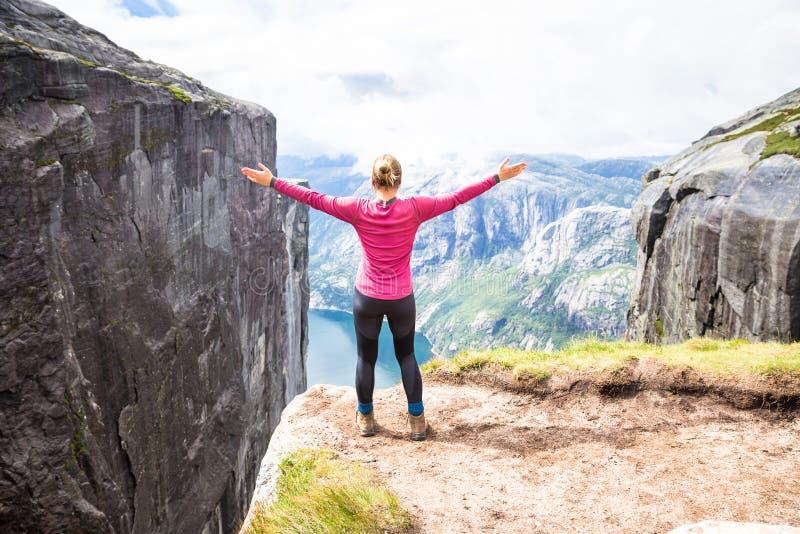 Jeune femme trimardant sur le kjerag La fille heureuse apprécient le beau lac et le temps beau en Norvège image libre de droits