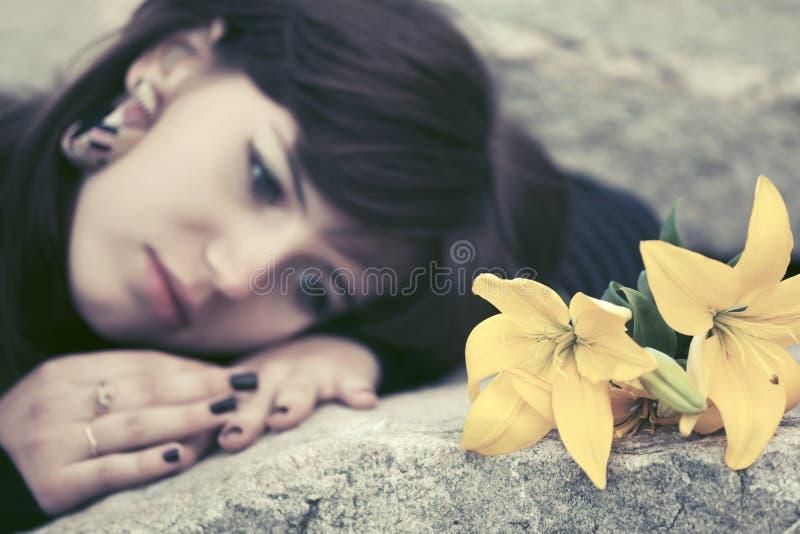 Jeune femme triste avec des fleurs se trouvant sur la pierre tombale photo stock