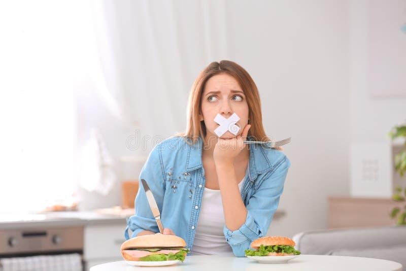 Jeune femme triste avec la bouche attachée du ruban adhésif et hamburgers à la table dans la cuisine image libre de droits