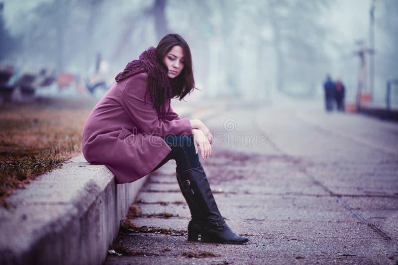 Jeune femme triste dans la dépression se reposant dehors photos stock