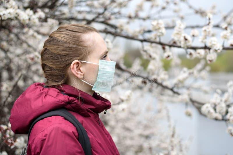 Jeune femme triste dans le masque protecteur m?dical protecteur Arbre de floraison sur le fond Allergie de ressort images libres de droits