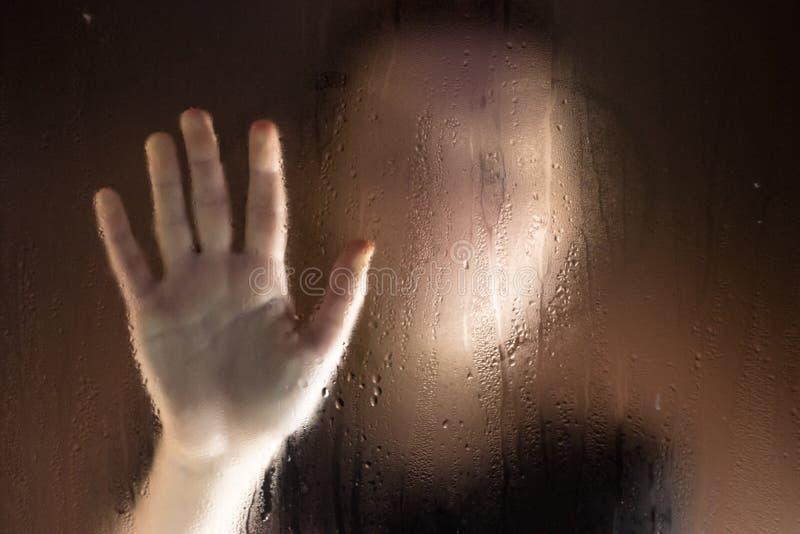 Jeune femme triste derrière toucher la fenêtre humide photo libre de droits