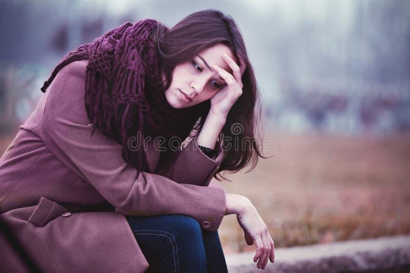 Jeune femme triste s'asseyant dehors images stock
