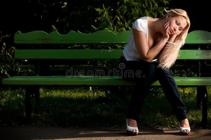 Jeune femme triste s'asseyant sur le banc en stationnement photo stock