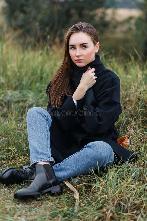 Jeune femme triste seul s'asseyant sur l'herbe dehors Espoir tristesse solitude Temps d'automne photographie stock