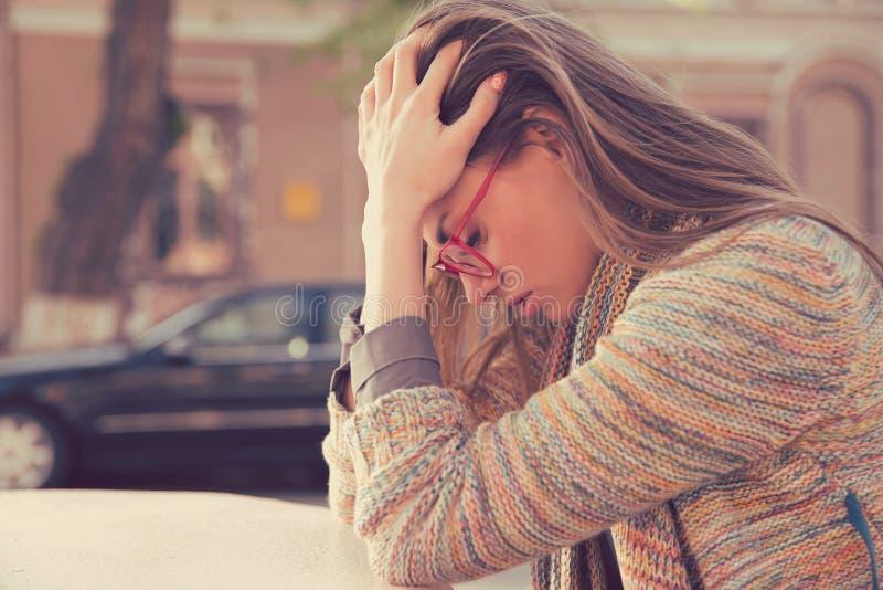 Jeune femme triste soumise à une contrainte par profil latéral s'asseyant dehors image stock