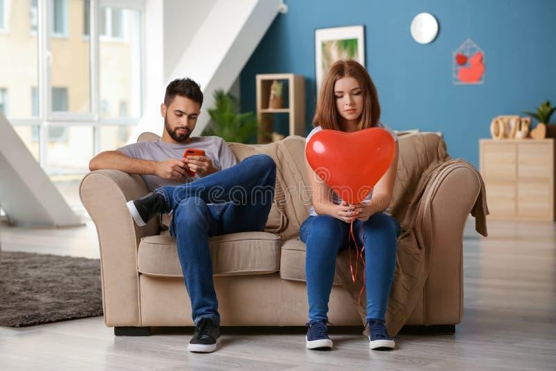 Jeune femme triste tenant le ballon en forme de coeur près de l'homme indifférent jouant avec le téléphone portable à la maison P images stock