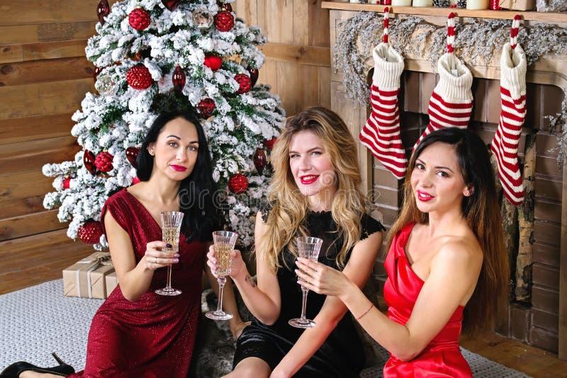Jeune femme trois avec un verre de champagne se reposant devant la cheminée et l'arbre de nouvelle année photo stock