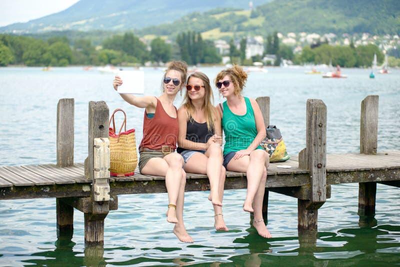 Jeune femme trois sur la plage avec leur téléphone photos stock