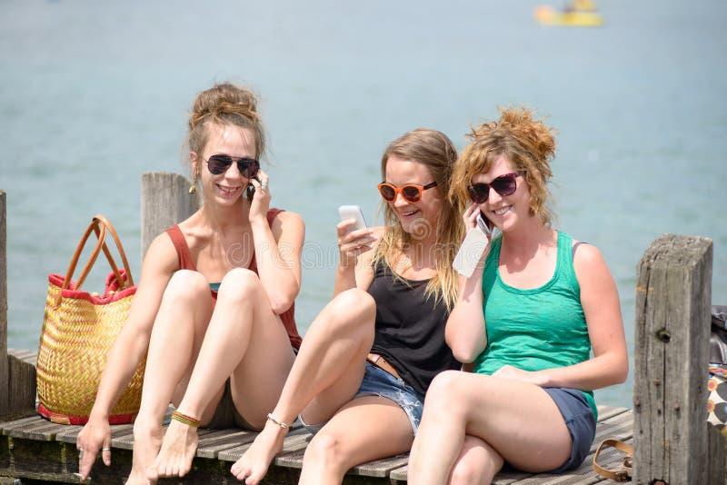 Jeune femme trois sur la plage avec leur téléphone photographie stock libre de droits