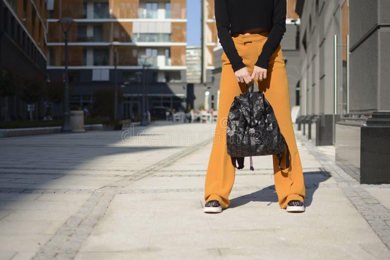 Jeune femme urbaine avec la mode et pantalon de sac à dos et orange noir moderne dans la rue de la ville européenne photographie stock libre de droits