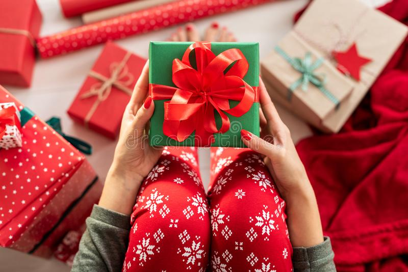 Jeune femme utilisant des pyjamas de Noël se reposant sur le plancher parmi les cadeaux de Noël enveloppés, tenant le beau boîte- photo stock