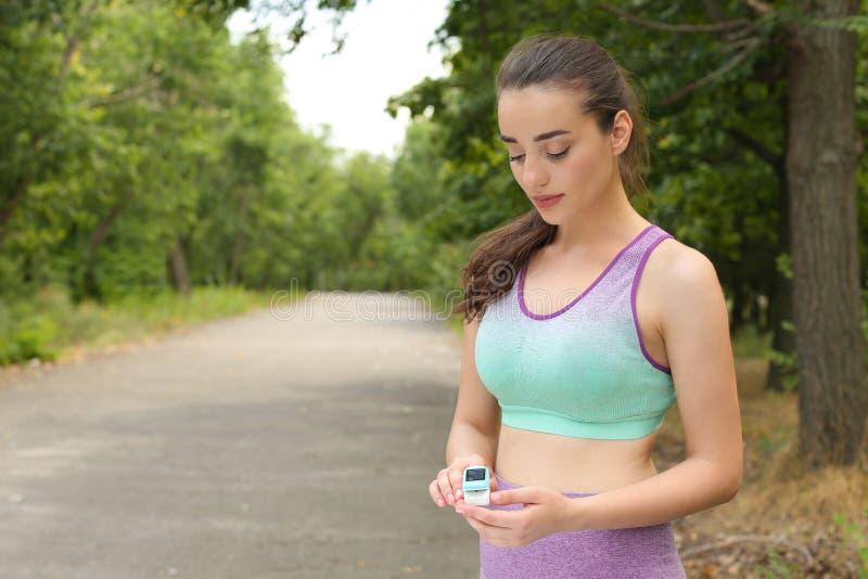 Jeune femme vérifiant avec le dispositif médical après la formation en parc L'espace pour le texte image libre de droits