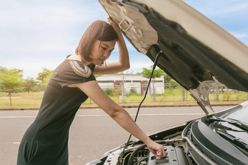 Jeune femme vérifiant avec réparer sa voiture cassée images libres de droits