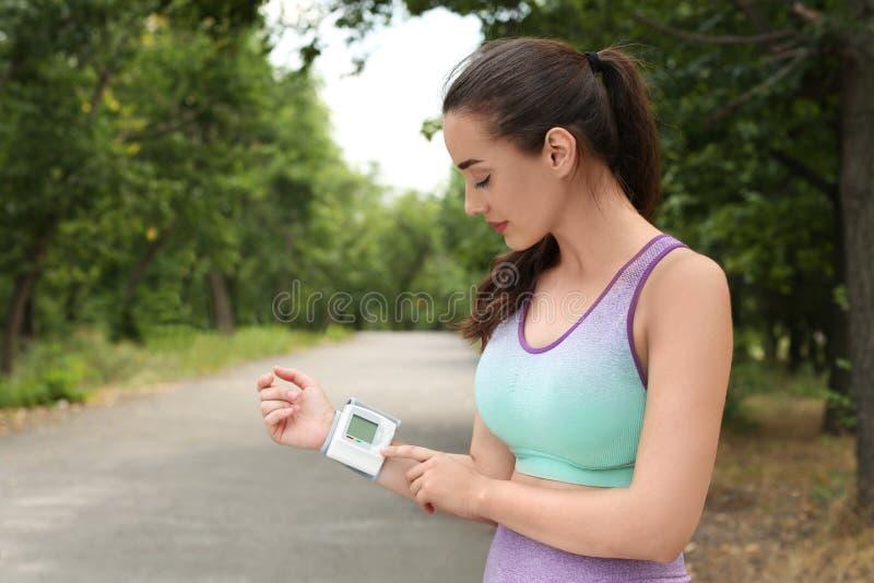Jeune femme vérifiant l'impulsion avec le dispositif après la formation en parc L'espace pour le texte images stock