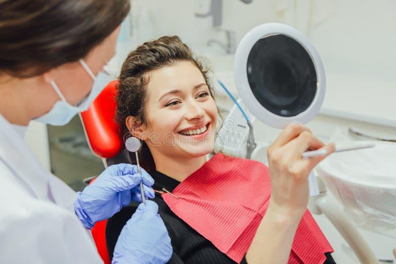 Jeune femme vérifiant leurs dents au miroir après traitement dentaire - bodycare de personnes et concept de stomatologie pour sai images stock