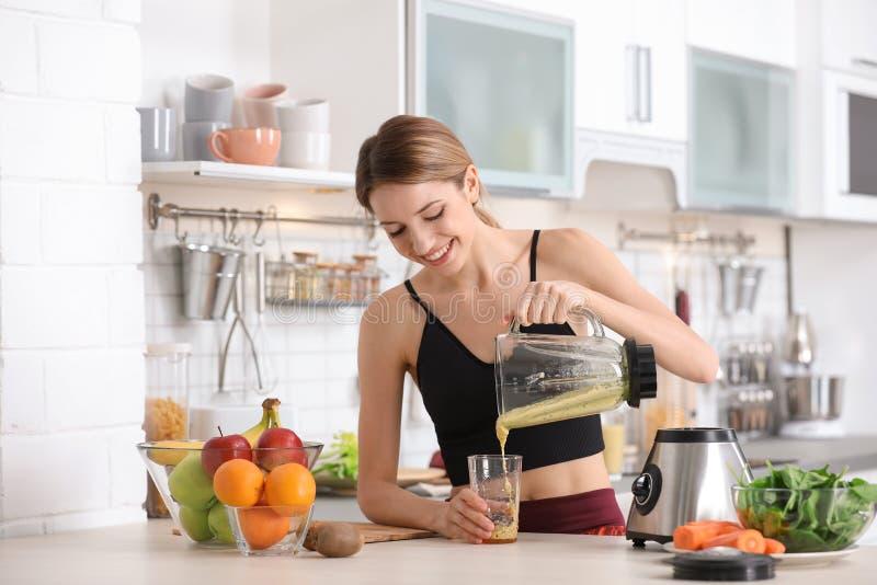 Jeune femme versant le smoothie sain savoureux dans le verre photos stock