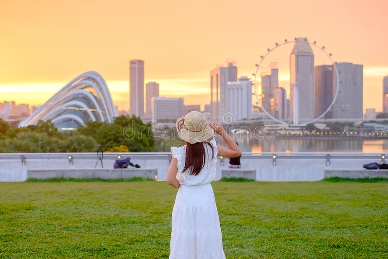 Jeune femme voyageant avec le chapeau au coucher du soleil, visite asiatique heureuse de voyageur dans le centre ville de ville d photo stock