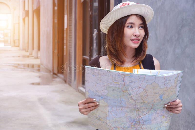 Jeune femme voyageuse tenant une carte en ville photos stock