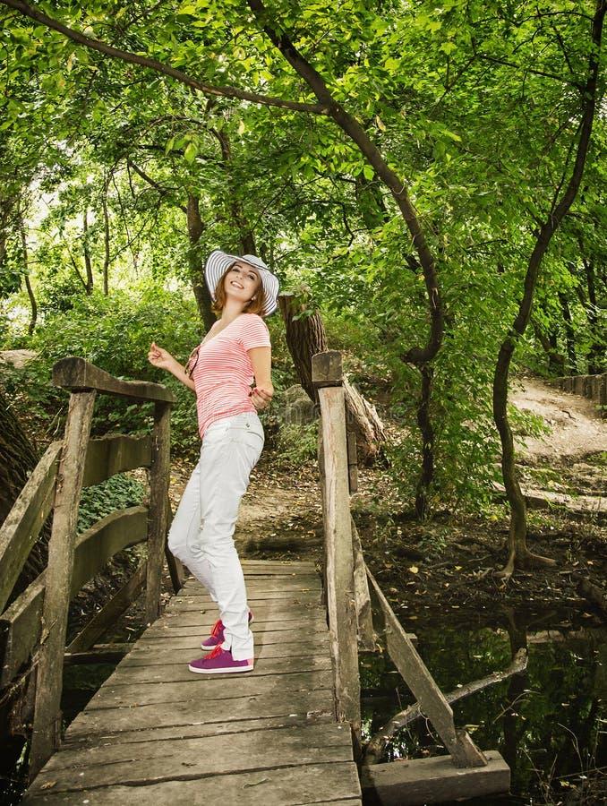 Jeune femme youful avec le chapeau de soleil posant sur le pont en bois photo libre de droits