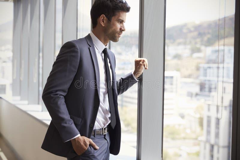 Jeune fenêtre de Looking Out Of d'homme d'affaires dans le bureau photographie stock libre de droits