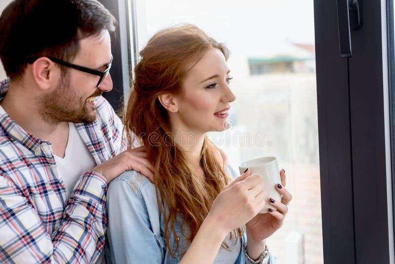 Jeune fenêtre se tenante prêt de couples mariés de leur nouvel appartement photographie stock