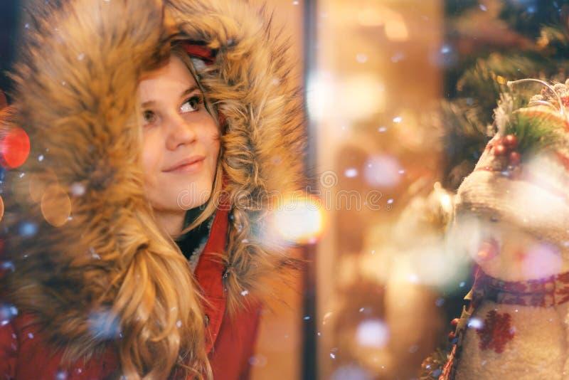 Jeune fille à la fenêtre de la boutique de Noël photographie stock