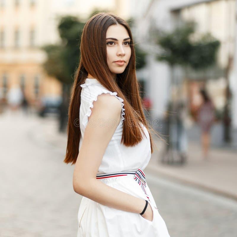 Jeune fille à la mode dans des vêtements blancs dans la ville images stock
