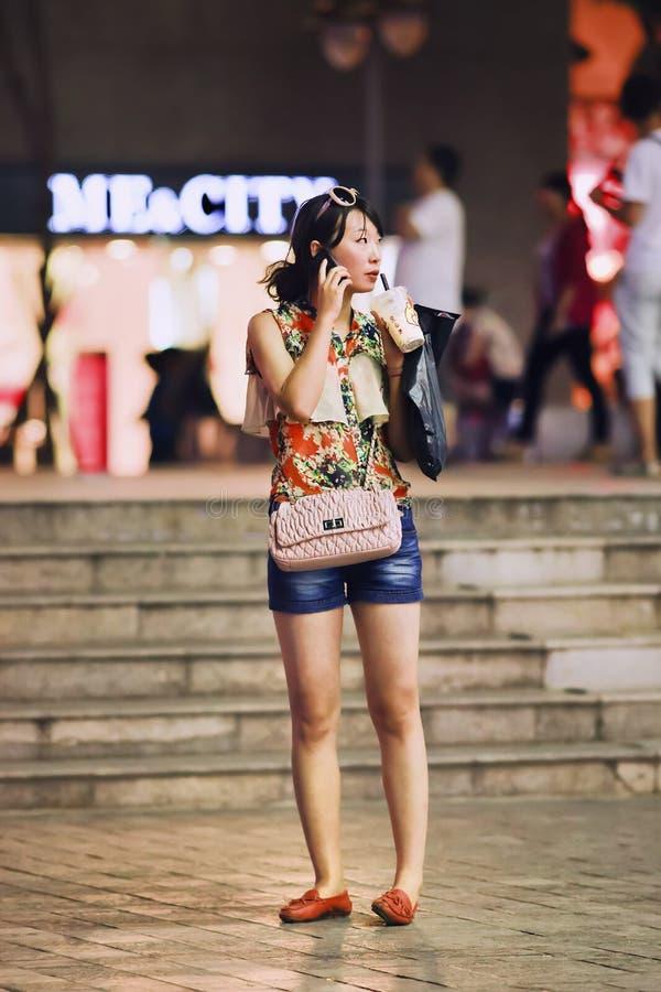 Jeune fille à la mode faisant un appel téléphonique, Kunming, Chine photographie stock