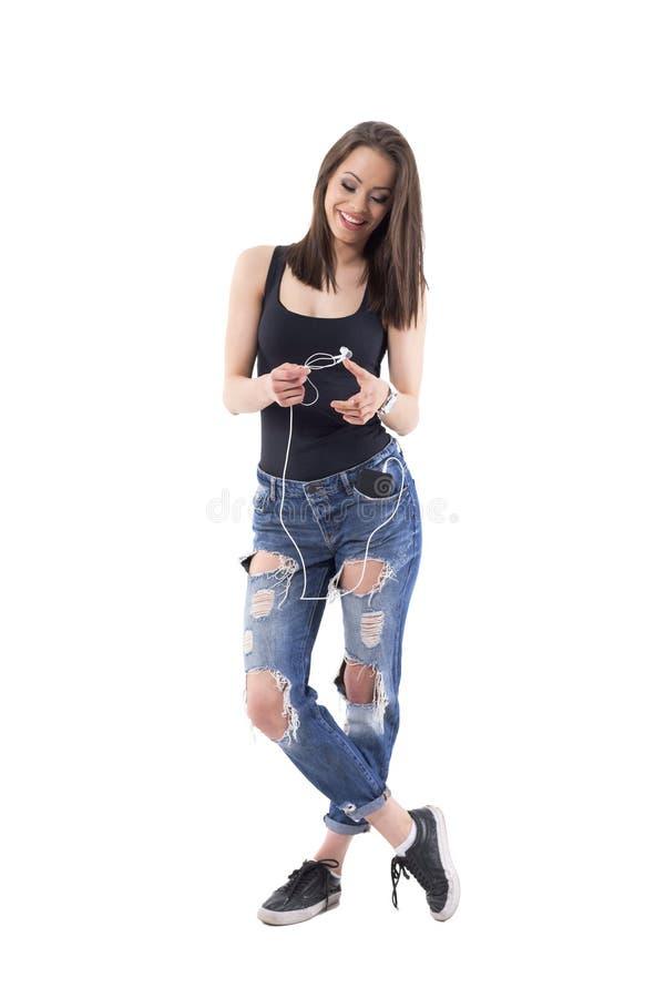 Jeune fille à la mode géniale fraîche jugeant des écouteurs fixés au téléphone portable dans la poche image libre de droits