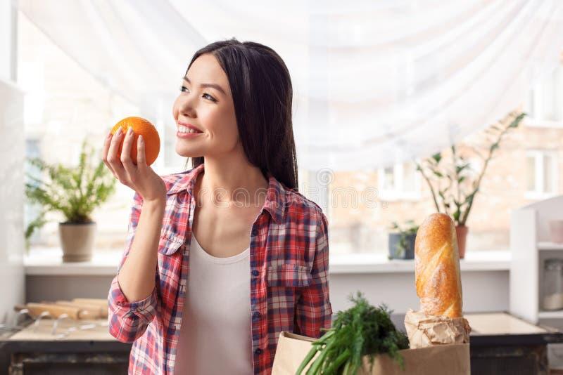 Jeune fille à la position saine de mode de vie de cuisine avec l'orange regardant rêver de fenêtre gai images stock