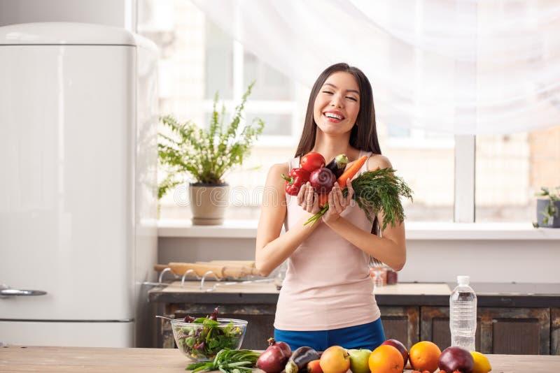 Jeune fille à la position saine de mode de vie de cuisine jugeant rire de légumes gai image stock