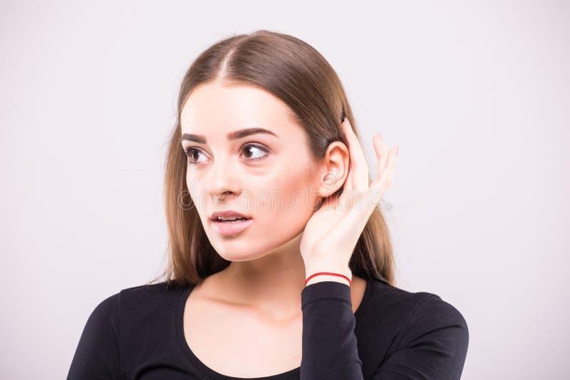 Jeune fille écoutant avec sa main sur une oreille photos libres de droits
