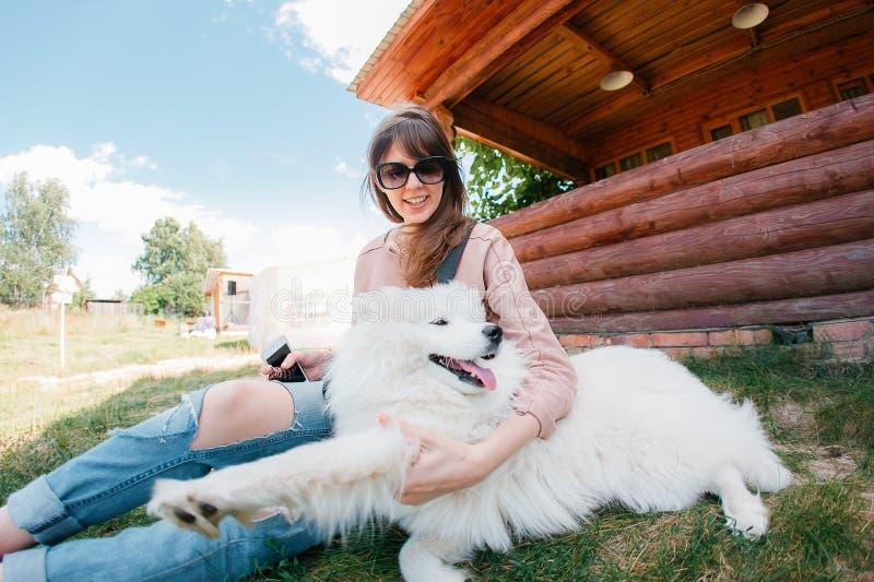 Jeune fille élégante de femme de hippie jouant le chien blanc d'enfant-peau dans le côté de pays photo libre de droits