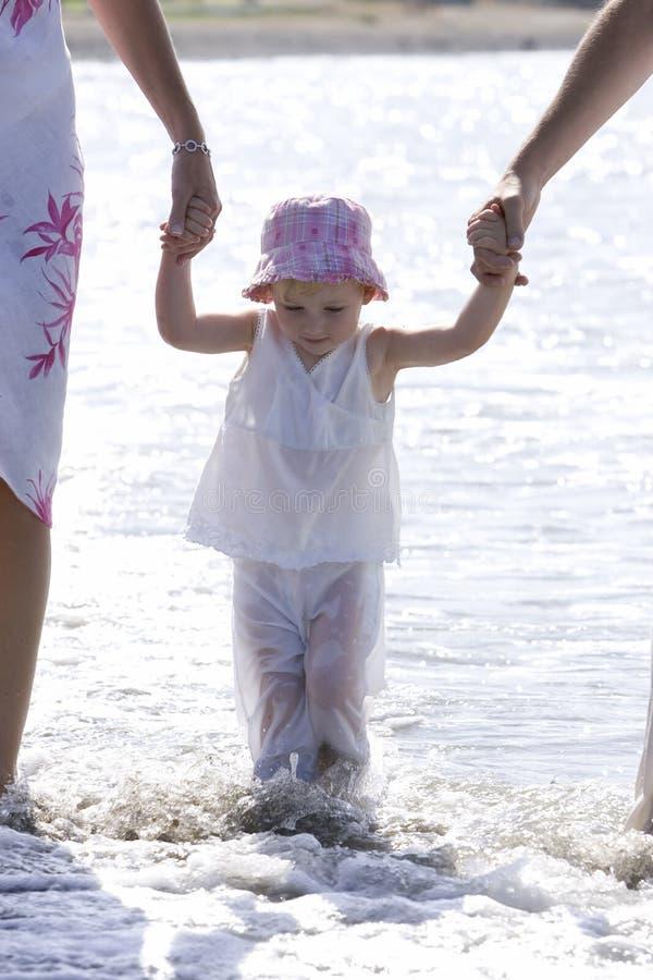 Jeune fille étant marchée sur la plage par des parents photos stock