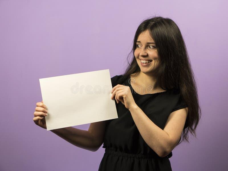 Jeune fille étonnée de brune tenant le conseil blanc vide vide Présentation de tract Mains de prise de brochure Exposition de fil images stock
