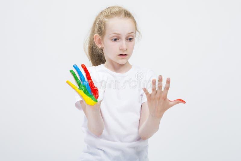 Jeune fille étonnée regardant les mains colorées malpropres brillamment peintes pendant le métier de peinture Contre le blanc photographie stock