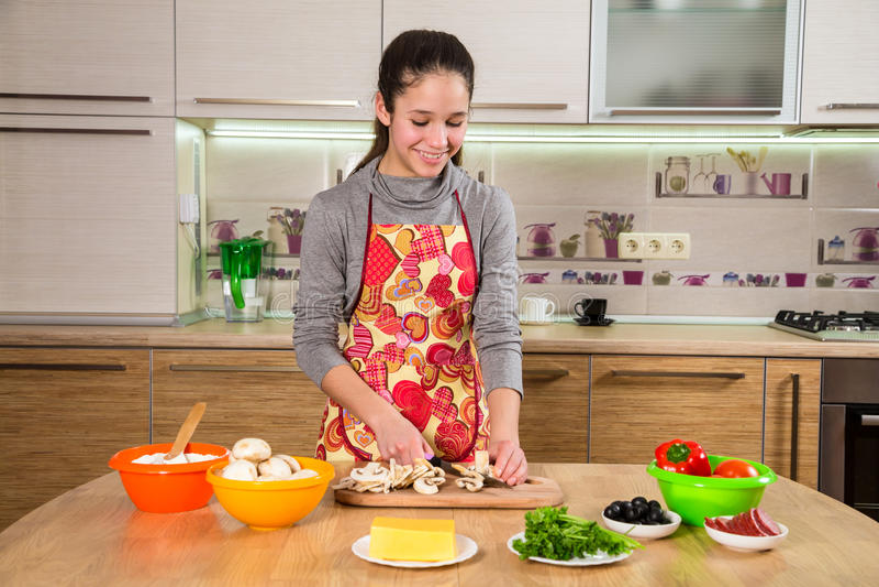 Jeune fille adorable coupant les champignons dans la cuisine photo libre de droits