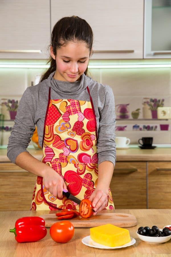 Jeune fille adorable coupant les tomates dans la cuisine photographie stock libre de droits