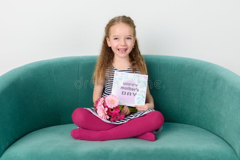 Jeune fille adorable s'asseyant sur un divan, tenant le bouquet de la carte rose de jour de marguerites de gerbera et de ` s de m photo stock