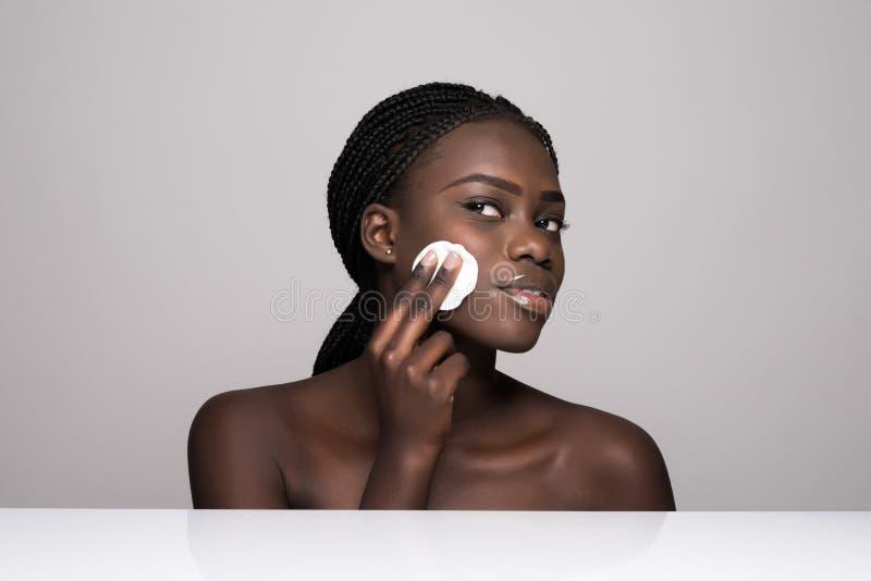 Jeune fille africaine appliquant la base sur son visage utilisant l'éponge de maquillage Portrait de fille africaine de sourire s photographie stock libre de droits