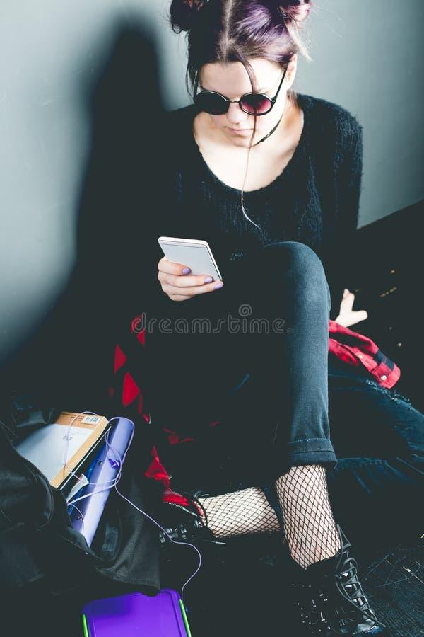Jeune fille alternative s'asseyant sur le plancher noir avec une école images stock
