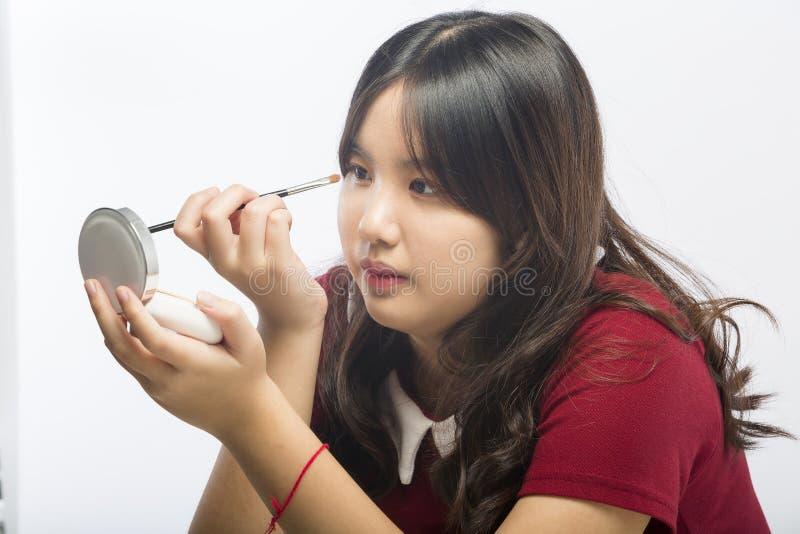 Jeune fille appliquant le fard à paupières coloré sur son oeil images stock