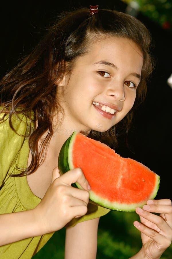 Jeune fille appréciant la pastèque photo stock