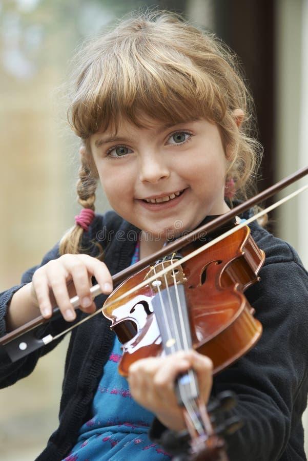 Jeune fille apprenant à jouer le violon photo libre de droits