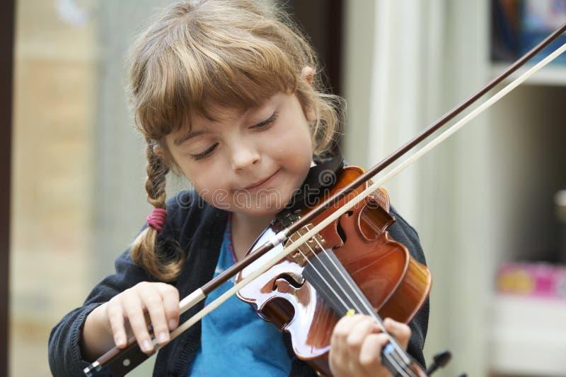 Jeune fille apprenant à jouer le violon photos stock