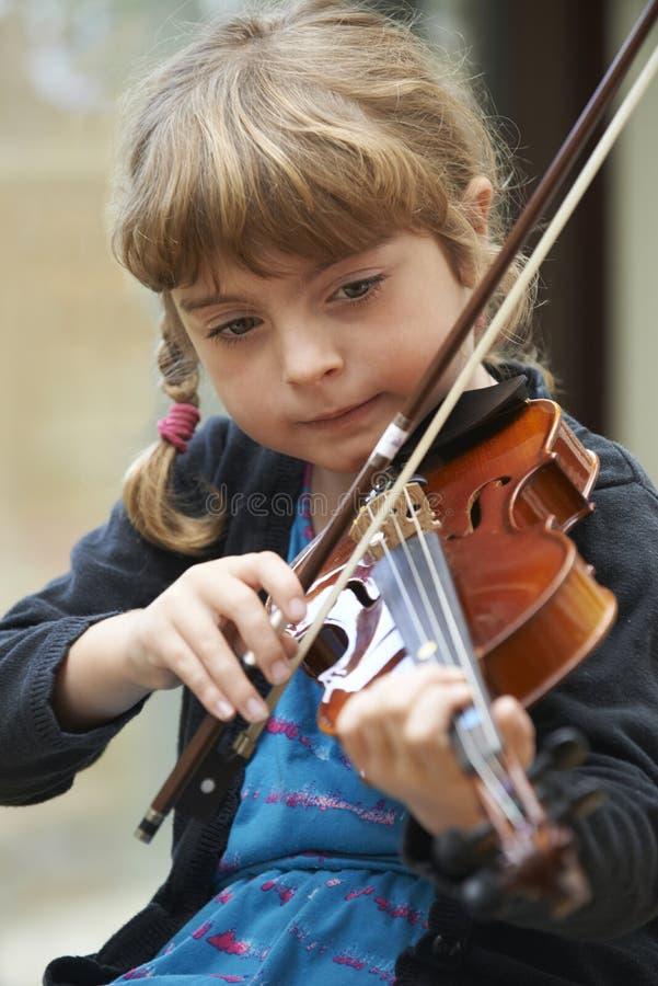 Jeune fille apprenant à jouer le violon photos libres de droits